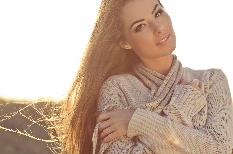 Beautiful young woman in sweater, hugging it close