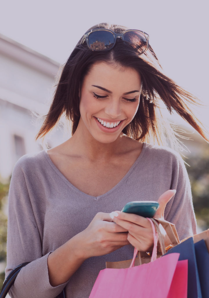 Young smiling woman with shopping bags, checking her wireless phone