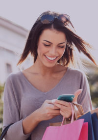 Young smiling woman checking her cell phone, holding shopping bags